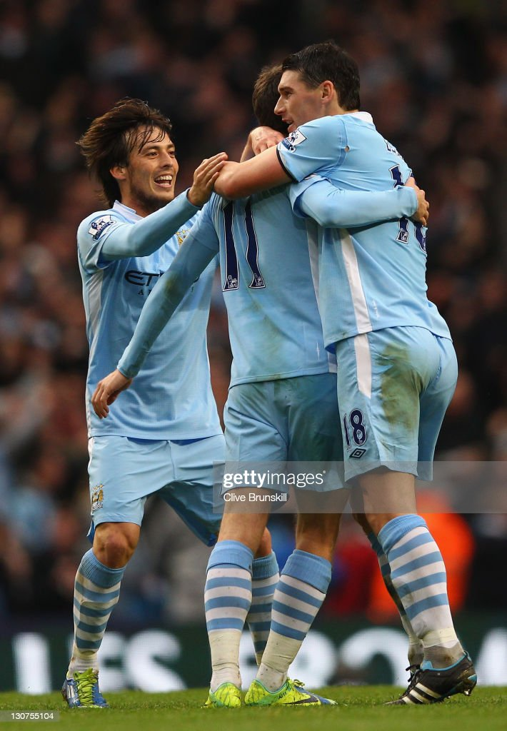 <a gi-track='captionPersonalityLinkClicked' href=/galleries/search?phrase=Adam+Johnson+-+Soccer+Player&family=editorial&specificpeople=6720094 ng-click='$event.stopPropagation()'>Adam Johnson</a> of Manchester City is congratulated by team mates <a gi-track='captionPersonalityLinkClicked' href=/galleries/search?phrase=Gareth+Barry&family=editorial&specificpeople=209123 ng-click='$event.stopPropagation()'>Gareth Barry</a> and <a gi-track='captionPersonalityLinkClicked' href=/galleries/search?phrase=David+Silva&family=editorial&specificpeople=675795 ng-click='$event.stopPropagation()'>David Silva</a> after scoring the third goal during the Barclays Premier League match between Manchester City and Wolverhampton Wanderers at Etihad Stadium on October 29, 2011 in Manchester, England.