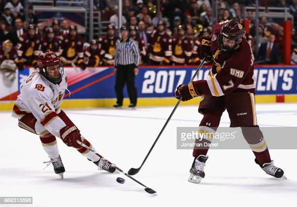 Adam Johnson of the MinnesotaDuluth Bulldogs fires a shot past Michael Davies of the Denver Pioneers during the 2017 NCAA Division I Men's Ice Hockey...