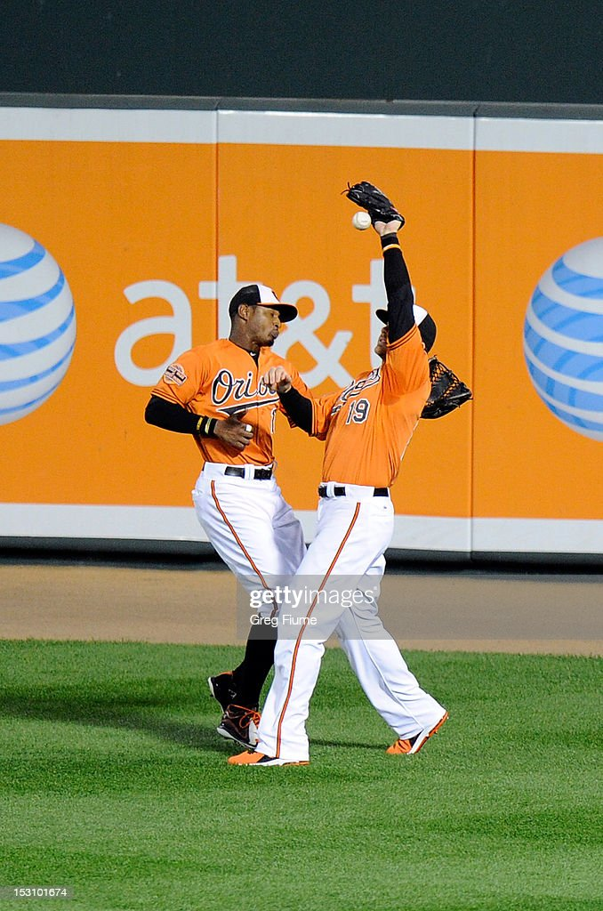 Adam Jones #10 and Chris Davis #19 of the Baltimore Orioles collide and drop a fly ball in the sixth inning against the Boston Red Sox at Oriole Park at Camden Yards on September 29, 2012 in Baltimore, Maryland.
