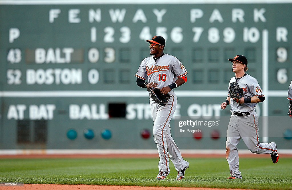 Adam Jones #10 and <a gi-track='captionPersonalityLinkClicked' href=/galleries/search?phrase=Nate+McLouth&family=editorial&specificpeople=536572 ng-click='$event.stopPropagation()'>Nate McLouth</a> #9 of the Baltimore Orioles celebrate a 9-6 win in the 12th inning against the Boston Red Sox at Fenway Park on September 22, 2012 in Boston, Massachusetts.