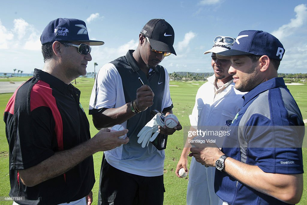 Adam Jones from Baltimore Orioles signs baseball balls during the David Ortiz 6th Celebrity Golf Classic at Punta Espada Golf Club on December 14, 2013 in Punta Cana, Dominican Republic.