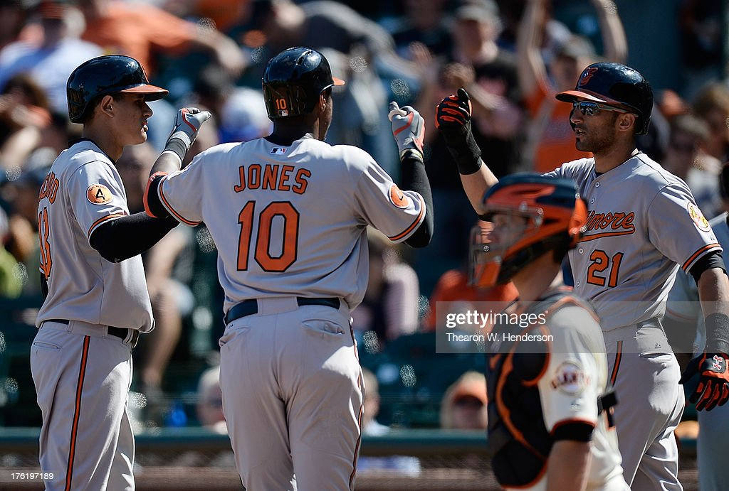Adam Jones #10, <a gi-track='captionPersonalityLinkClicked' href=/galleries/search?phrase=Manny+Machado&family=editorial&specificpeople=5591039 ng-click='$event.stopPropagation()'>Manny Machado</a> #13 and <a gi-track='captionPersonalityLinkClicked' href=/galleries/search?phrase=Nick+Markakis&family=editorial&specificpeople=614708 ng-click='$event.stopPropagation()'>Nick Markakis</a> #21 of the Baltimore Orioles celebrate a three-run homer hit by Jones in the ninth inning against the San Francisco Giants at AT&T Park on August 11, 2013 in San Francisco, California. Machado and Markakis was on base when Jones hit the home run.