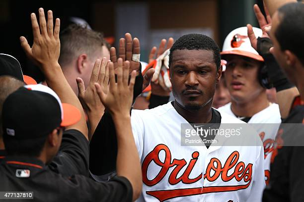 Adam Jones of the Baltimore Orioles and teammate Manny Machado are greeted in the dugout after both scoring in the first inning against the New York...