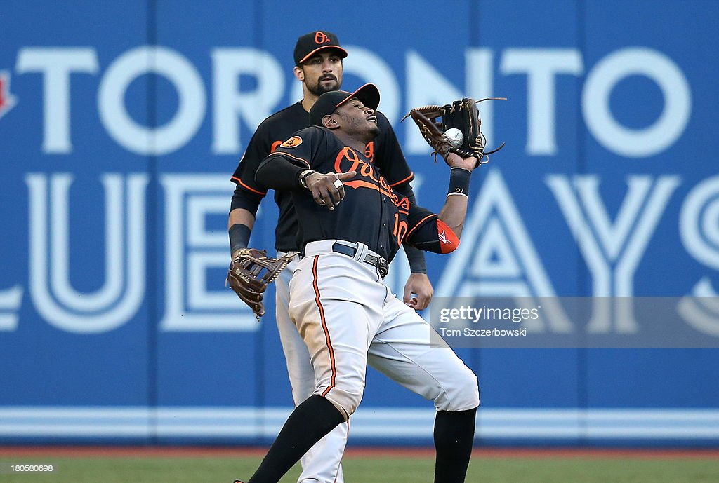 Adam Jones #10 of the Baltimore Orioles catches a fly ball in front of teammate <a gi-track='captionPersonalityLinkClicked' href=/galleries/search?phrase=Nick+Markakis&family=editorial&specificpeople=614708 ng-click='$event.stopPropagation()'>Nick Markakis</a> #21 in the eighth inning during MLB game action against the Toronto Blue Jays on September 14, 2013 at Rogers Centre in Toronto, Ontario, Canada.