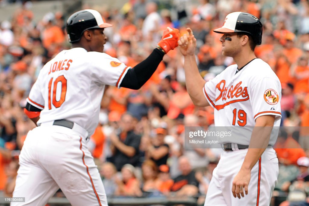 Adam Jones #10 of the Baltimore Orioles celbrates a two run home run in the third inning with Chris Davis #19 during a baseball game against the Colorado Rockies on August 18, 2013 at Oriole Park at Camden Yards in Baltimore, Maryland.