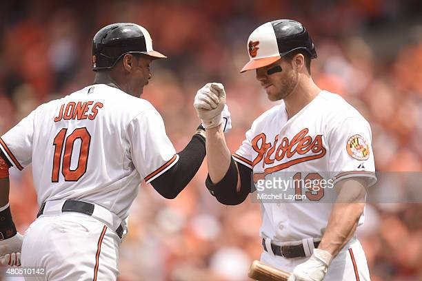 Adam Jones of the Baltimore Orioles celebrates a solo home run in the second inning with Chris Davis during a baseball game against the Baltimore...
