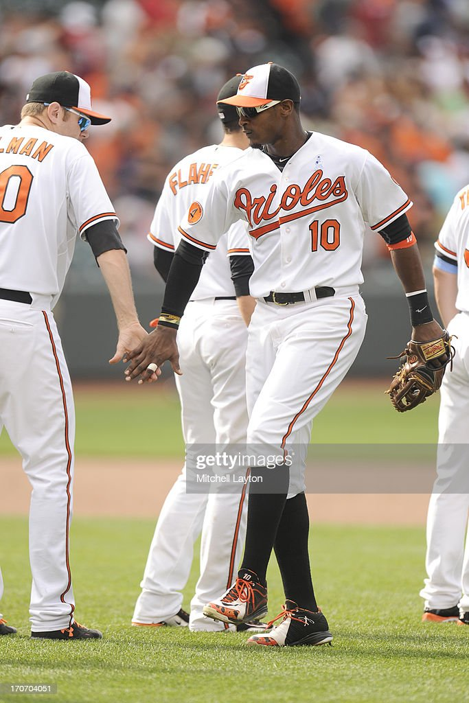 Adam Jones #10 of the Baltimore Orioles celebrates a win with Chris Tillman #30 after a baseball game on June 16, 2013 at Oriole Park at Camden Yards in Baltimore, Maryland. The Orioles won 6-3.