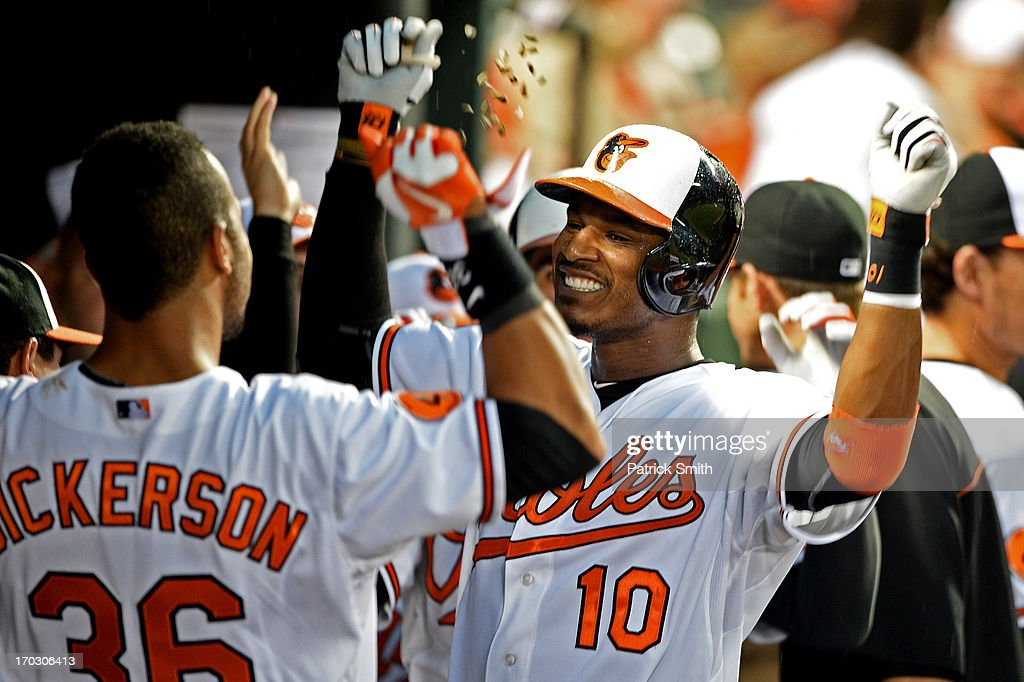 Adam Jones #10 of the Baltimore Orioles celebrates in the dugout with teammate Chris Dickerson #36 after hitting a two-run home run in the fourth inning against the Los Angeles Angels of Anaheim at Oriole Park at Camden Yards on June 10, 2013 in Baltimore, Maryland.