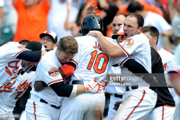 Adam Jones of the Baltimore Orioles celebrates scoring the game winning run off a double by Matt Wieters with Mark Reynolds and Steve Pearce during...