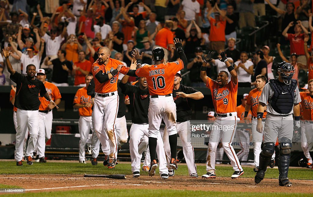 Adam Jones #10 of the Baltimore Orioles celebrates scoring with teammate <a gi-track='captionPersonalityLinkClicked' href=/galleries/search?phrase=Nick+Markakis&family=editorial&specificpeople=614708 ng-click='$event.stopPropagation()'>Nick Markakis</a> #21 during the thirteenth inning to defeat the Detroit Tigers 8-6 at Oriole Park at Camden Yards on July 14, 2012 in Baltimore, Maryland.