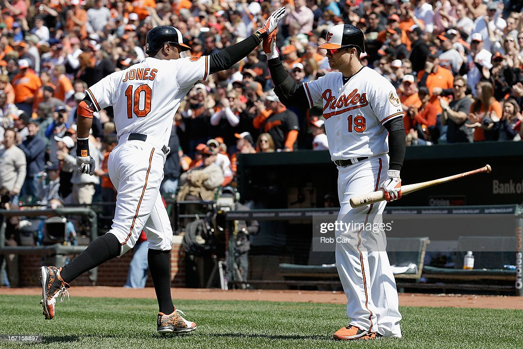 Adam Jones #10 of the Baltimore Orioles celebrates with Chris Davis #19 after hitting a solo home run against the Los Angeles Dodgers at Oriole Park at Camden Yards on April 21, 2013 in Baltimore, Maryland.