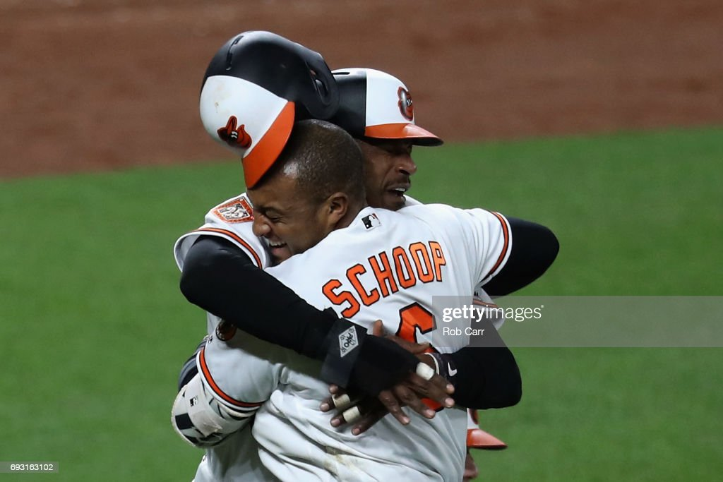 Adam Jones #10 of the Baltimore Orioles celebrates with Jonathan Schoop #6 after scoring the winning run in the tenth inning to give the Orioles a 6-5 win over the Pittsburgh Pirates at Oriole Park at Camden Yards on June 6, 2017 in Baltimore, Maryland.