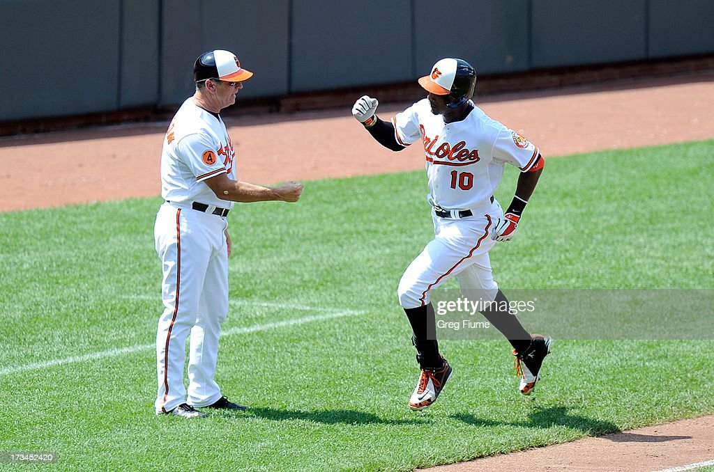 Adam Jones #10 of the Baltimore Orioles celebrates with third base coach Bobby Dickerson after hitting a home run in the fifth inning against the Toronto Blue Jays at Oriole Park at Camden Yards on July 14, 2013 in Baltimore, Maryland.