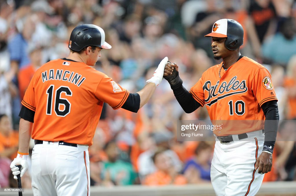 Adam Jones #10 of the Baltimore Orioles celebrates with Trey Mancini #16 after scoring in the third inning against the Detroit Tigers at Oriole Park at Camden Yards on August 5, 2017 in Baltimore, Maryland.