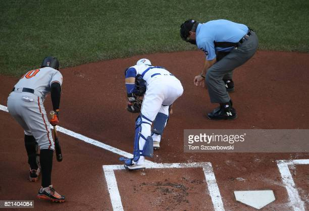 Adam Jones of the Baltimore Orioles gets help from Russell Martin of the Toronto Blue Jays and home plate umpire Angel Hernandez in picking up the...