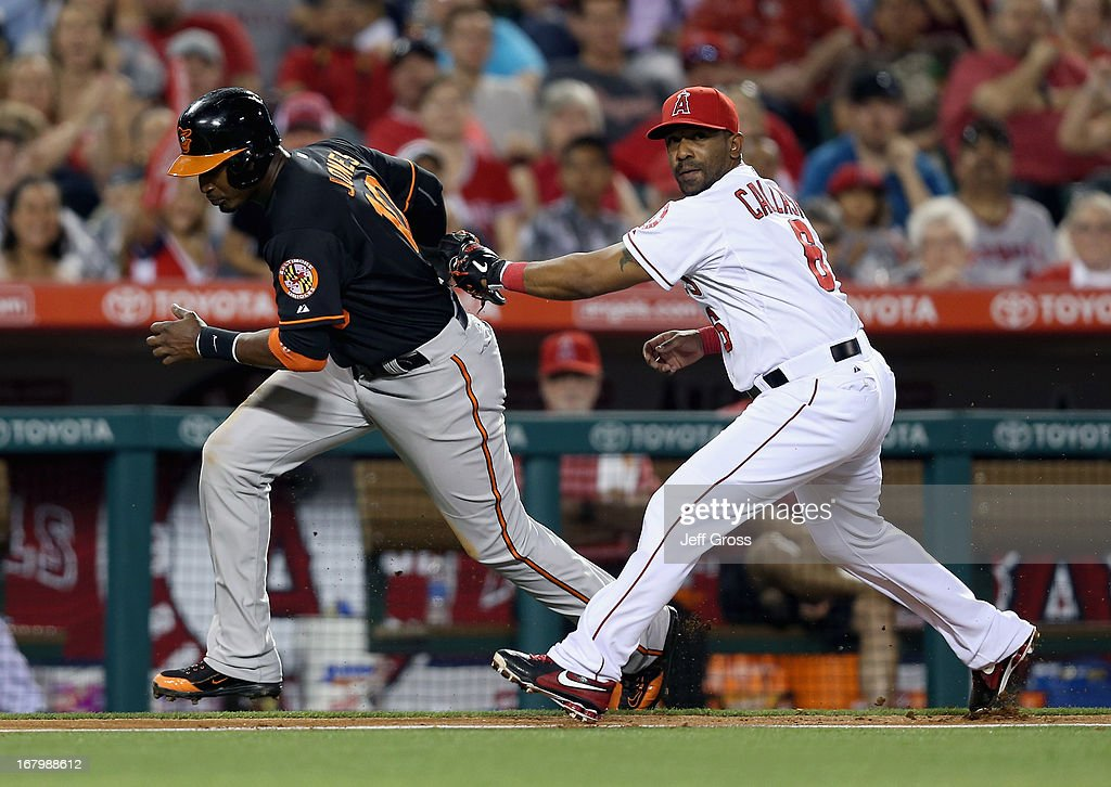 Adam Jones #10 of the Baltimore Orioles is caught in a run down by third baseman Alberto Callaspo #6 of the Los Angeles Angels of Anaheim in the seventh inning at Angel Stadium of Anaheim on May 3, 2013 in Anaheim, California.