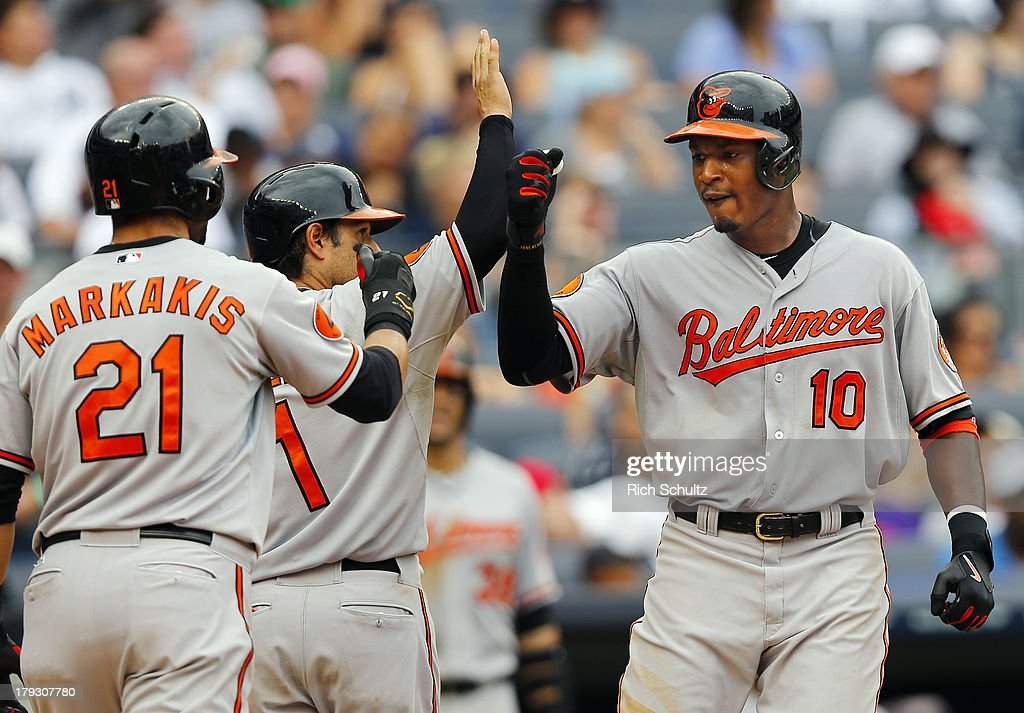 Adam Jones #10 of the Baltimore Orioles is congratulated by teammates <a gi-track='captionPersonalityLinkClicked' href=/galleries/search?phrase=Nick+Markakis&family=editorial&specificpeople=614708 ng-click='$event.stopPropagation()'>Nick Markakis</a> #21 and Brian Roberts #1 after he hit a three run home run during the seventh inning of a MLB baseball game against the New York Yankees at Yankee Stadium on September 1, 2013 in the Bronx borough of New York City.