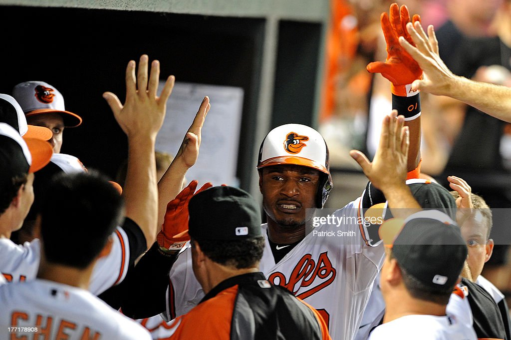 Adam Jones #10 of the Baltimore Orioles is greeted in the dugout after hitting a solo home run against the Tampa Bay Rays in the third inning at Oriole Park at Camden Yards on August 21, 2013 in Baltimore, Maryland. The Baltimore Orioles won, 4-2.
