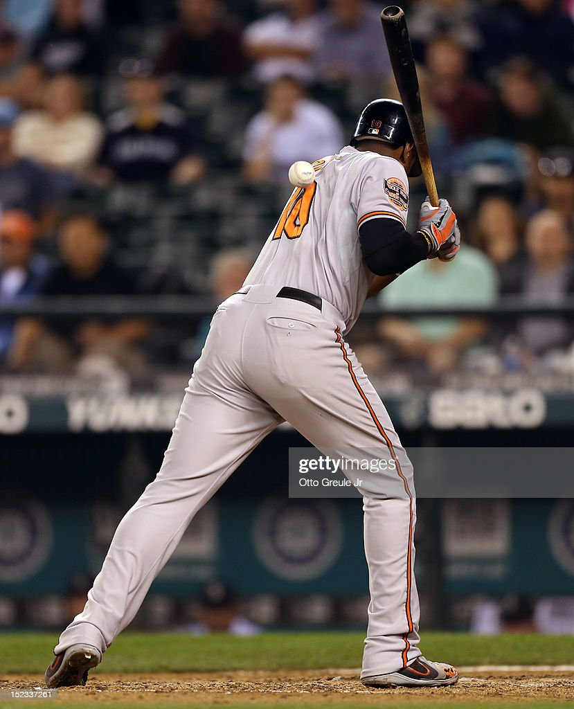 Adam Jones #10 of the Baltimore Orioles is hit by a pitch in the eleventh inning against the Seattle Mariners at Safeco Field on September 18, 2012 in Seattle, Washington.