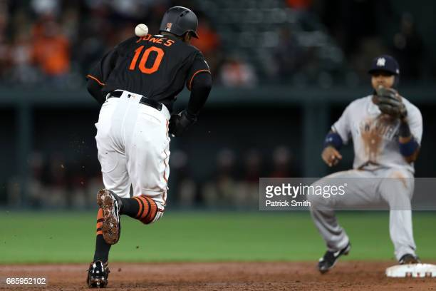 Adam Jones of the Baltimore Orioles is hit with a throw by third baseman Chase Headley of the New York Yankees as he attempts to tag up during the...
