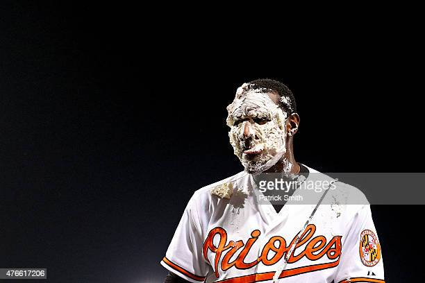 Adam Jones of the Baltimore Orioles licks pie from his face following being hit in the face by teammate Manny Machado after defeating the Boston Red...
