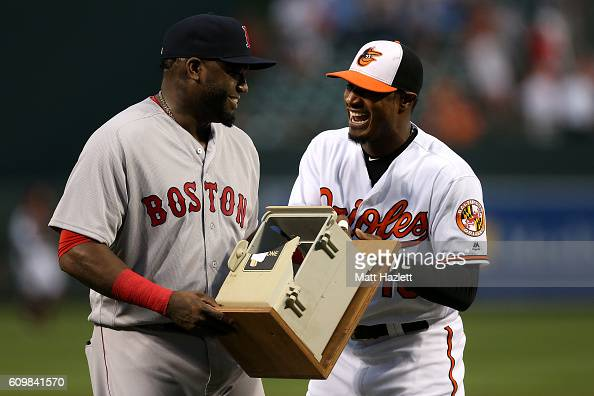 Adam Jones of the Baltimore Orioles presents David Ortiz of the Boston Red Sox with the dugout telephone Ortiz broke on July 27 2013 during his...