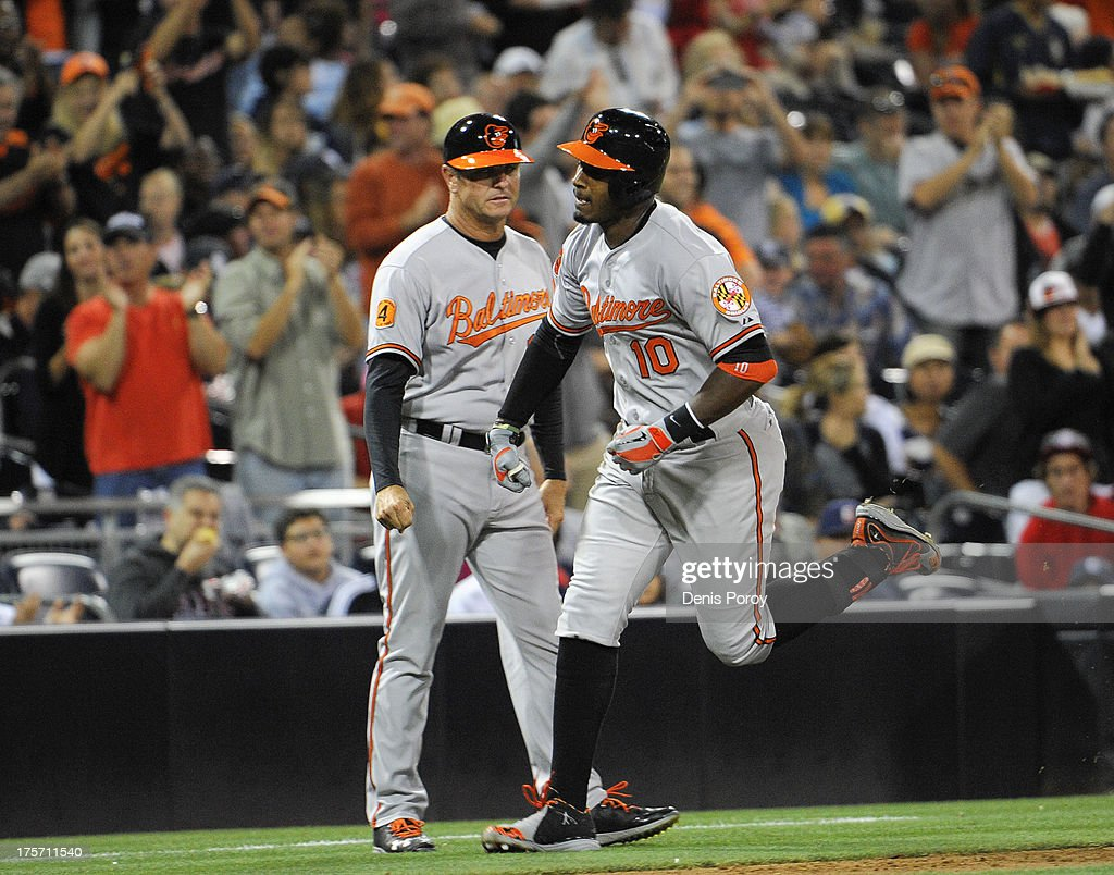 Adam Jones #10 of the Baltimore Orioles, right, is congratulated by third base coach Bobby Dickerson #11 after he hit a solo home run during the fourth inning of a baseball game against the San Diego Padres at Petco Park on August 6, 2013 in San Diego, California.