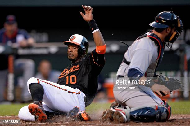 Adam Jones of the Baltimore Orioles scores off of a Chris Davis RBI double in front of catcher Yan Gomes of the Cleveland Indians in the third inning...