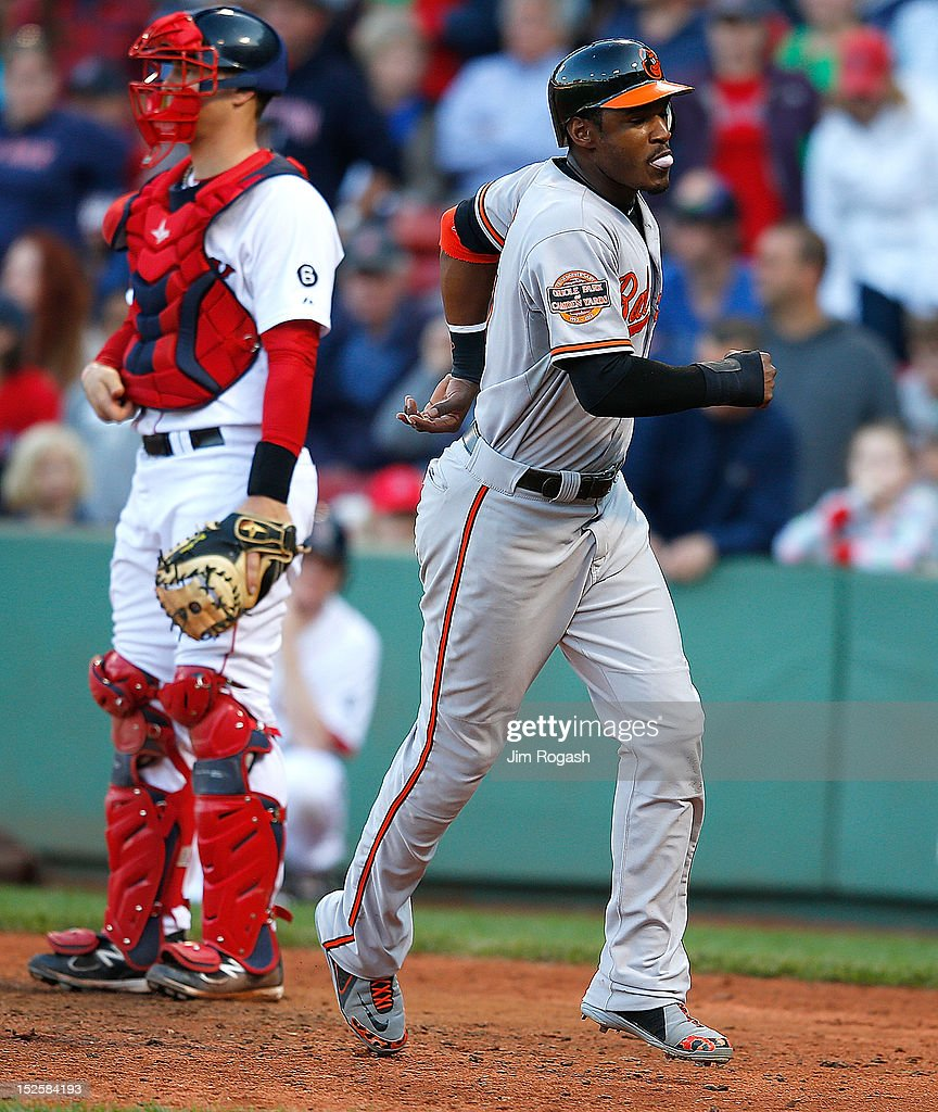 Adam Jones #10 of the Baltimore Orioles scores the winning run on a hit by Jim Thome #25 in the 12th inning as Ryan Lavarnway #60 of the Boston Red Sox looks away at Fenway Park on September 22, 2012 in Boston, Massachusetts.