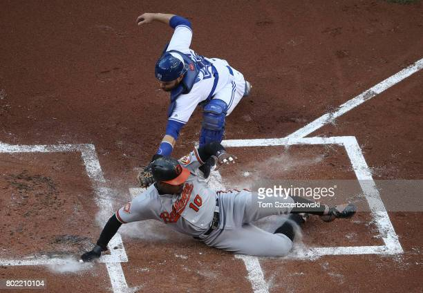 Adam Jones of the Baltimore Orioles slides across home plate safely to score a run on a tworun double by Mark Trumbo in the first inning during MLB...