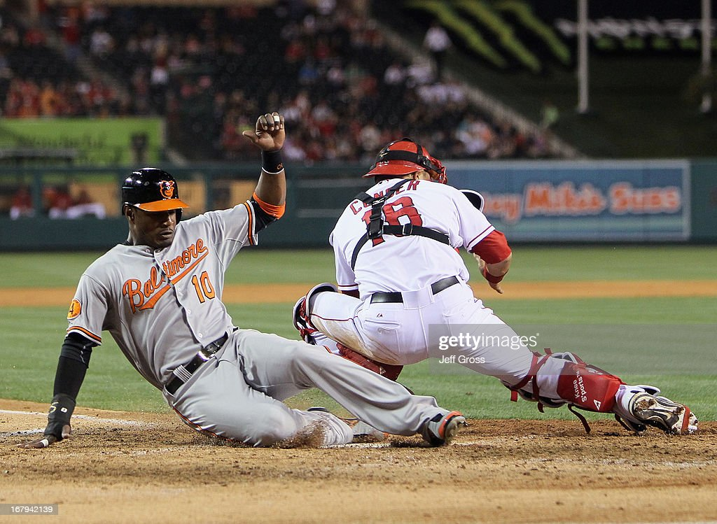 Adam Jones #10 of the Baltimore Orioles slides safely into home past catcher <a gi-track='captionPersonalityLinkClicked' href=/galleries/search?phrase=Hank+Conger&family=editorial&specificpeople=713039 ng-click='$event.stopPropagation()'>Hank Conger</a> #16 of the Los Angeles Angels of Anaheim in the seventh inning at Angel Stadium of Anaheim on May 2, 2013 in Anaheim, California.