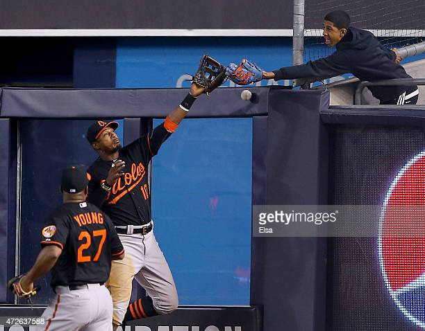 Adam Jones of the Baltimore Orioles tries to make a catch on a hit by Alex Rodriguez of the New York Yankees as a fan also goes for the ball in the...