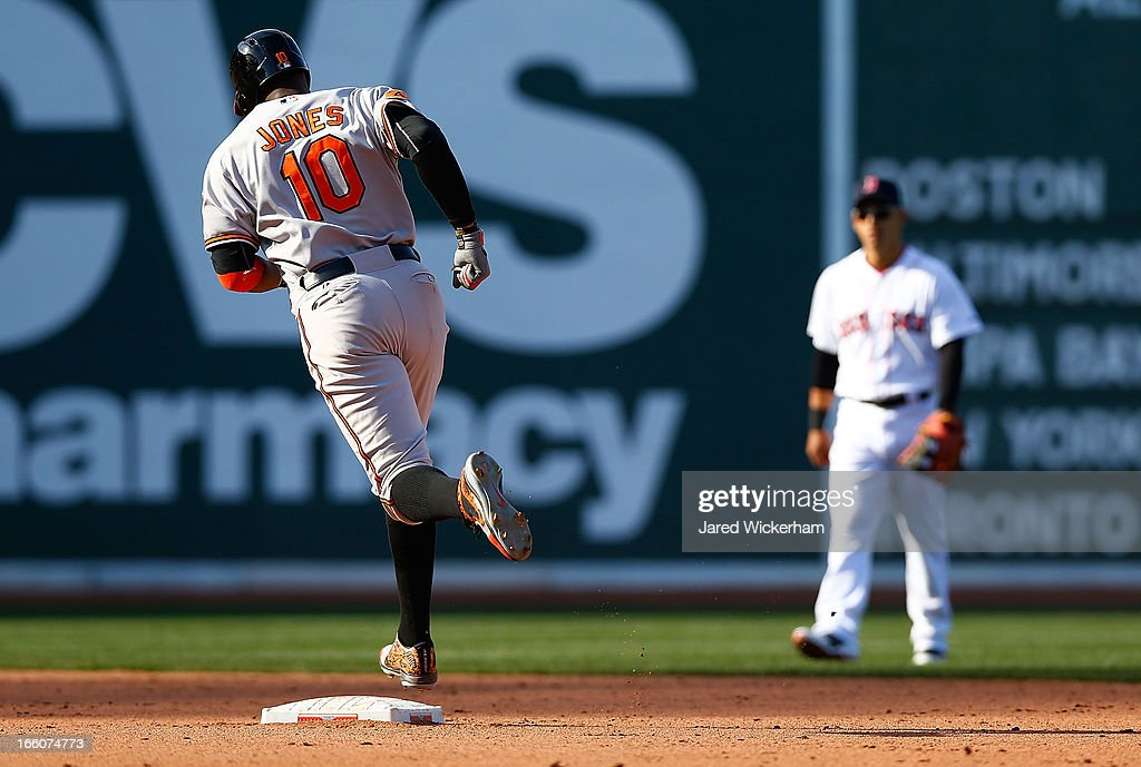 Adam Jones #10 of the Baltimore Orioles trots around second base after hitting a solo home run in the ninth inning off of Joel Hanrahan #52 of the Boston Red Sox during the Opening Day game on April 8, 2013 at Fenway Park in Boston, Massachusetts.