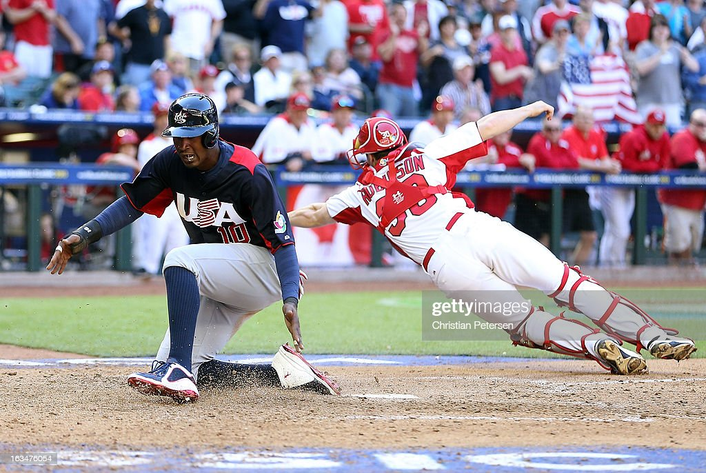 Adam Jones #10 of USA scores a run past catcher Chris Robinson #30 of Canada during the eighth inning of the World Baseball Classic First Round Group D game at Chase Field on March 10, 2013 in Phoenix, Arizona.