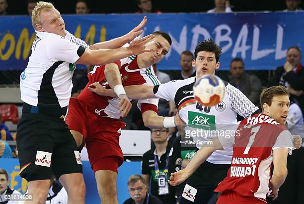 Adam Juhasz of Hungary is challenged by Patrick Wiencek and Simon Ernst of Germany during the 25th IHF Men's World Championship 2017 match between...