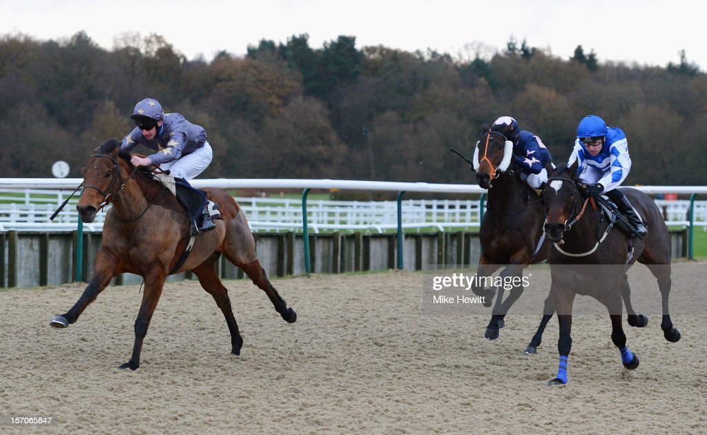 Adam Kirby on Corporal Maddox on their way to winning the Betfred 'The Home Of Goals Galore' Claiming Stakes from Robert Winston and Majuro (R) at Lingfield Park on November 28, 2012 in Lingfield, England.