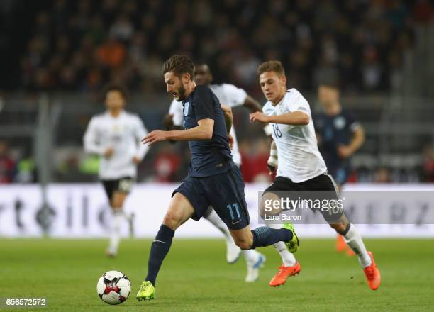 Adam Lallana of England is put under pressure from Joshua Kimmich of Germany during the international friendly match between Germany and England at...