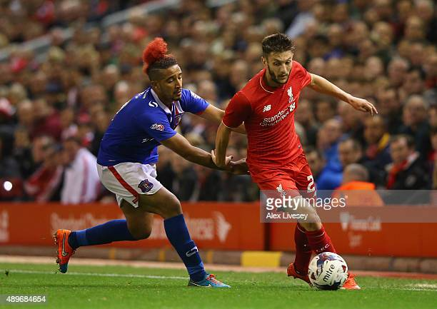 Adam Lallana of Liverpool beats Bastien Hery of Carlisle United during the Capital One Cup Third Round match between Liverpool and Carlisle United at...