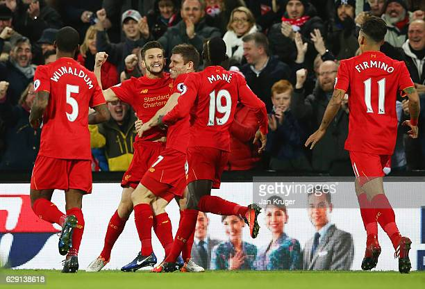 Adam Lallana of Liverpool celebrates scoring the opening goal with his team mates during the Premier League match between Liverpool and West Ham...