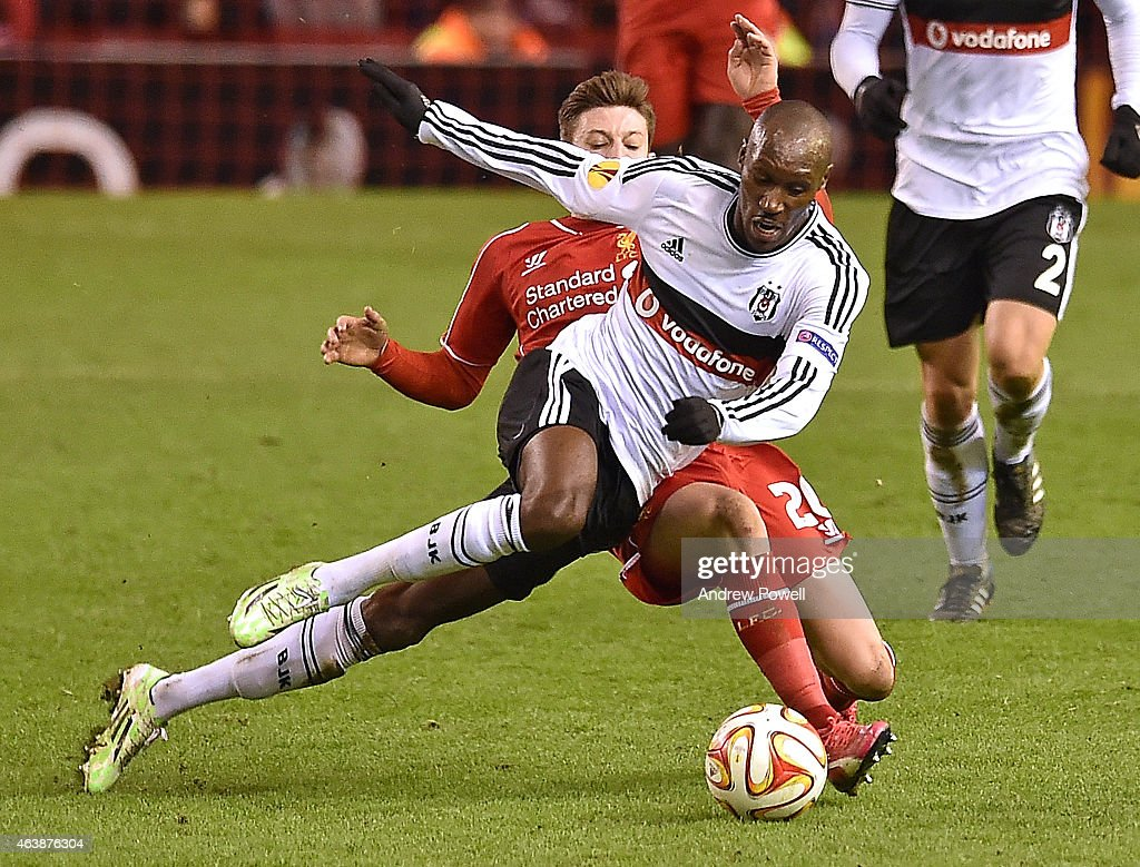 Adam Lallana of Liverpool competes with Atiba Hutchinson of Besiktas during the UEFA Europa League Round of 32 match between Liverpool FC and Besiktas JK on February 19, 2015 in Liverpool, United Kingdom.