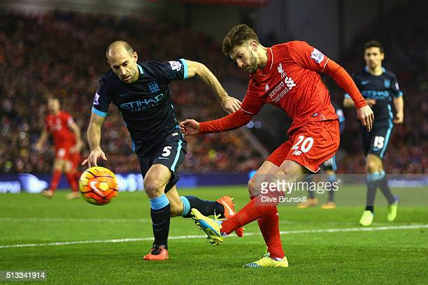 Adam Lallana of Liverpool crosses the ball under pressure from Pablo Zabaleta of Manchester City in action during the Barclays Premier League match...