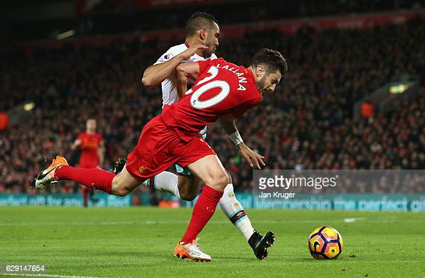 Adam Lallana of Liverpool is challenged by Dimitri Payet of West Ham United in the penalty area during the Premier League match between Liverpool and...