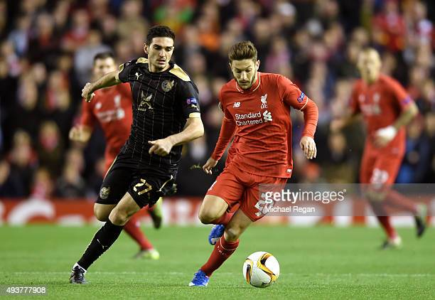 Adam Lallana of Liverpool is pursued by Magomed Ozdoev of Rubin Kazan during the UEFA Europa League Group B match between Liverpool FC and Rubin...