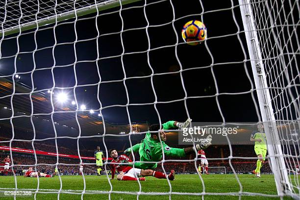 Adam Lallana of Liverpool scores his team's third goal past Victor Valdes of Middlesbrough during the Premier League match between Middlesbrough and...