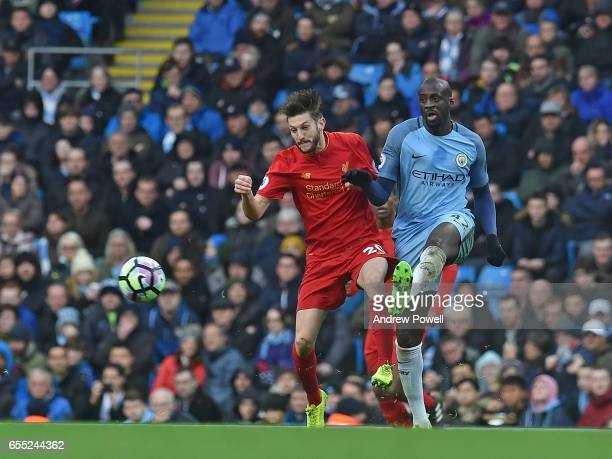 Adam Lallana of Liverpool with YaYa Toure of Man City during the Premier League match between Manchester City and Liverpool at Etihad Stadium on...