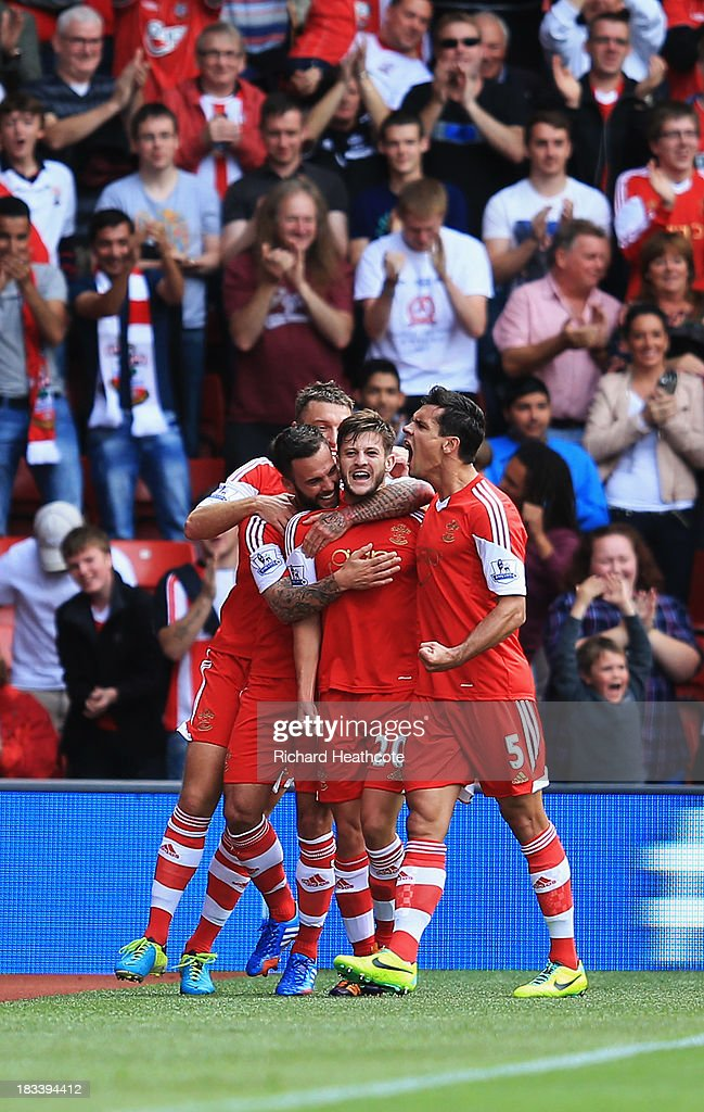 <a gi-track='captionPersonalityLinkClicked' href=/galleries/search?phrase=Adam+Lallana&family=editorial&specificpeople=5475862 ng-click='$event.stopPropagation()'>Adam Lallana</a> of Southampton (20) celebrates with team mates as he scores their first goal during the Barclays Premier League match between Southampton and Swansea City at St Mary's Stadium on October 6, 2013 in Southampton, England.