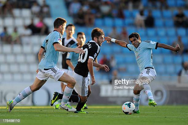 Adam Lallana of Southampton duels for the ball with Augusto Fernandez and Andreu Fontas of RC Celta de Vigo during a friendly match between RC Celta...