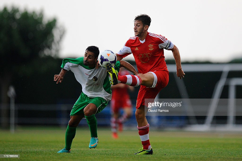 Adam Lallana of Southampton duels for the ball with Marc Garcia of UE Llagostera during a friendly match between Southampton FC and UE Llagostera at the Josep Pla i Arbones Stadium on July 17, 2013 in Girona, Spain.