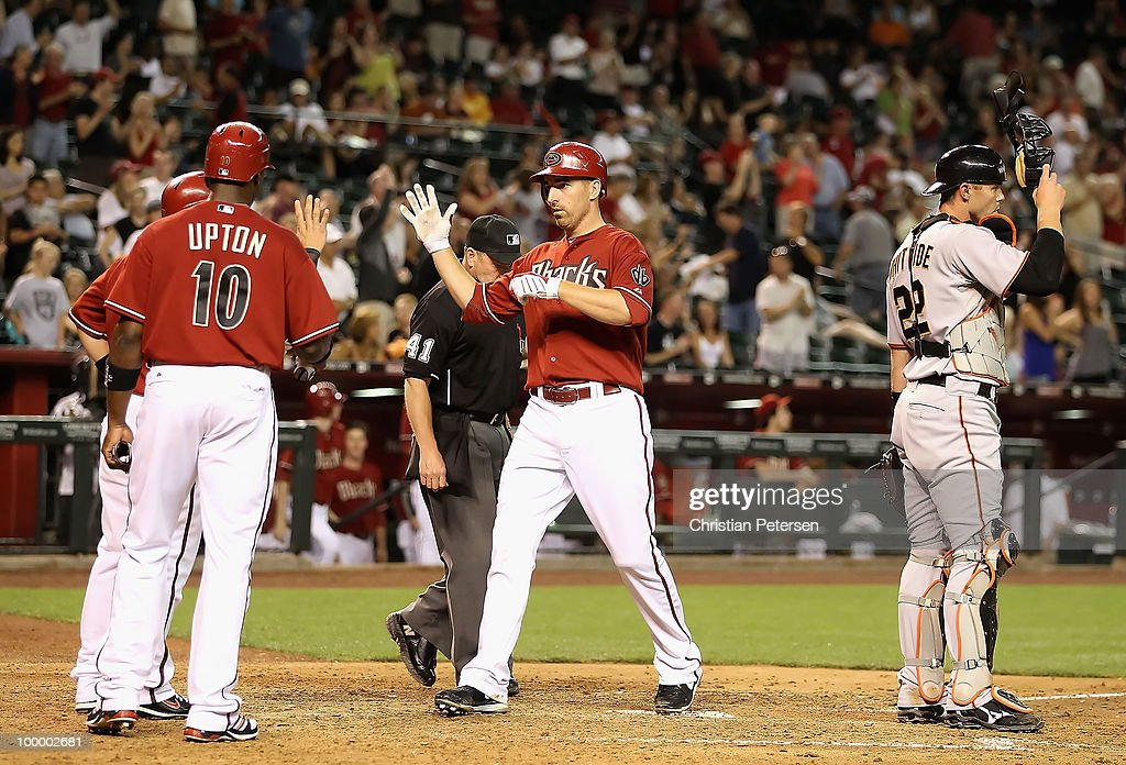 Adam LaRoche #25 of the Arizona Diamondbacks is congratulated by teammate Justin Upton #10 after hitting a 3 run home run against the San Francisco Giants during the eighth inning of the Major League Baseball game at Chase Field on May 19, 2010 in Phoenix, Arizona. The Diamondbacks defeated the Giants 13-1.