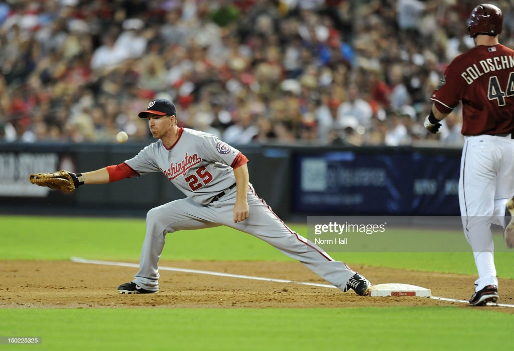 Adam LaRoche of the Washington Nationals cant come up with a throw in the dirt as Paul Goldschmidt of the Arizona Diamondbacks runs to first base at...
